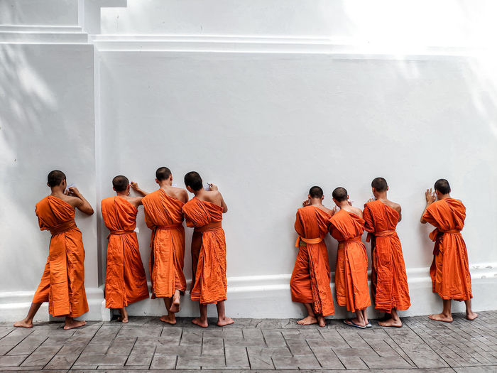 Rear view of monks standing against wall