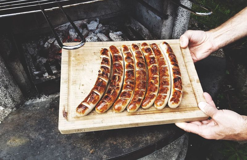 Cropped Hand Holding Wooden Board With Grilled Sausages By Oven