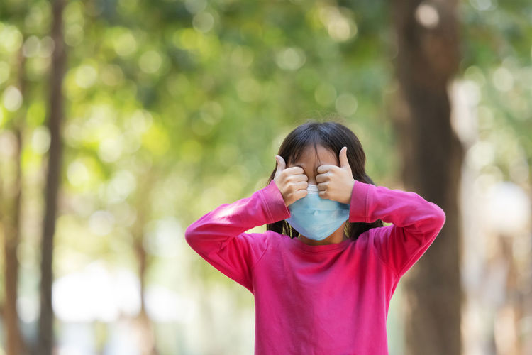 Cute girl wearing mask covering eyes while standing outdoors