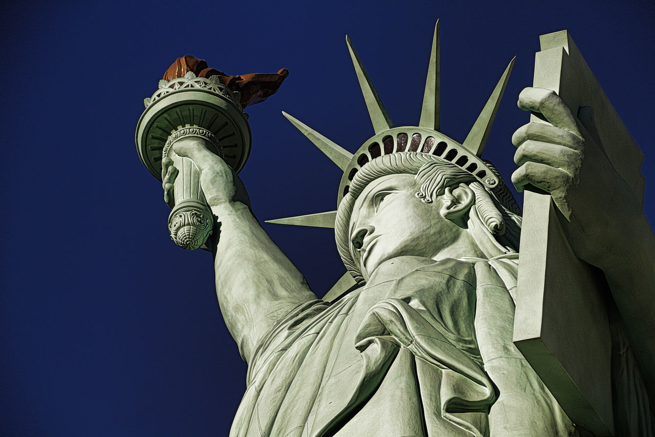 statue, female likeness, travel destinations, human representation, freedom, sculpture, low angle view, symbol, outdoors, day, crown, no people, clear sky, sky, close-up