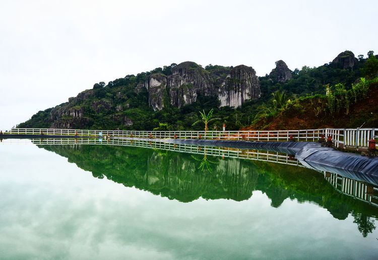 When morning at Embung Nglanggeran, Gunung Kidul, Yogyakarta, Indonesia. Water Sky Reflection Nature Waterfront Architecture Built Structure Beauty In Nature Mountain Tree Scenics - Nature Tranquility No People Tranquil Scene Day Plant Bridge Connection Lake Outdoors EyeEmNewHere EyeEm Best Shots EyeEm Nature Lover EyeEm Gallery EyeEm Selects