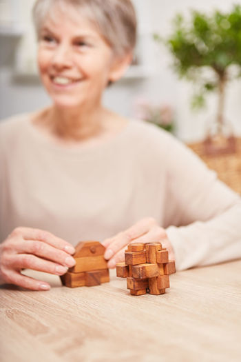 Adult Close-up Day Dementia Focus On Foreground Front View Holding Human Hand Indoors  Leisure Activity Leisure Games One Person People Playing Real People Senior Adult Senior Woman Senior Women Sitting Table Wood - Material