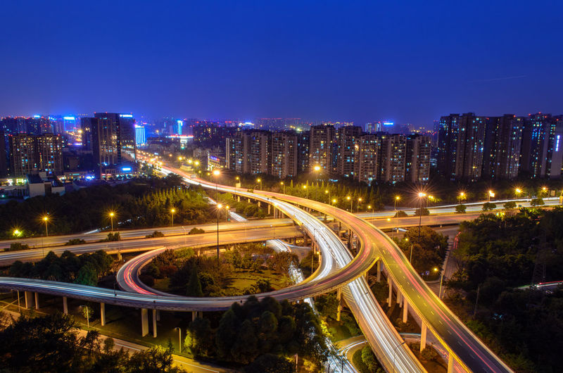 ILLUMINATED MODERN HIGHWAYS AGAINST CITYSCAPE BY NIGHT