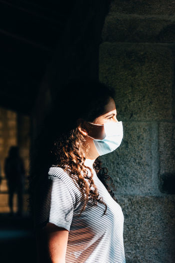 Side view of woman standing against window wearing face mask