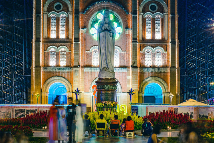 People pray in front of the Notre Dame Cathedral of Saigon in Ho Chi Minh City, Vietnam. In front of is the Virgin Mary statue. According to legend, one day shed tears.... Architecture Built Structure Arch Building Exterior Building Religion Place Of Worship Spirituality Belief Group Of People Travel Destinations Motion City The Past Real People Blurred Motion History Illuminated Notre Dame Cathedral Of Saigon Saigon Protection Ho Chi Minh City Vietnam Virgin Mary Sculpture Legend,