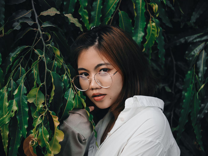Portrait of beautiful young woman with plants