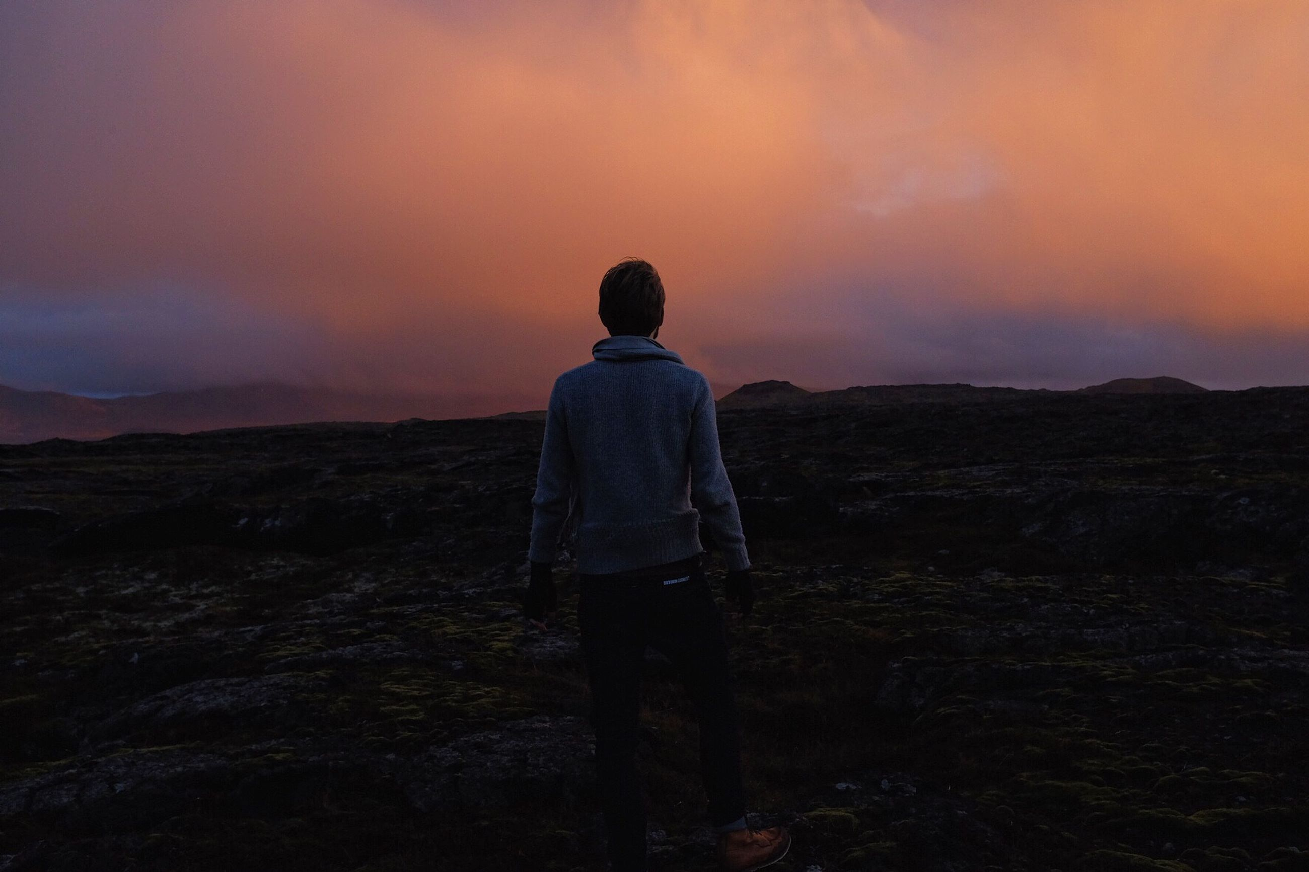 sunset, mountain, tranquil scene, landscape, sky, rear view, tranquility, scenics, standing, beauty in nature, lifestyles, leisure activity, nature, men, cloud - sky, full length, mountain range, orange color