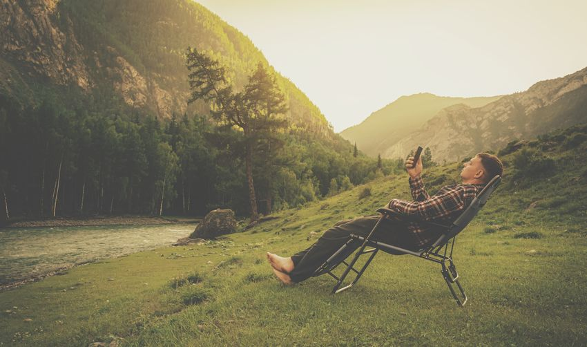 Side view of man relaxing on chair using smart phone against mountain