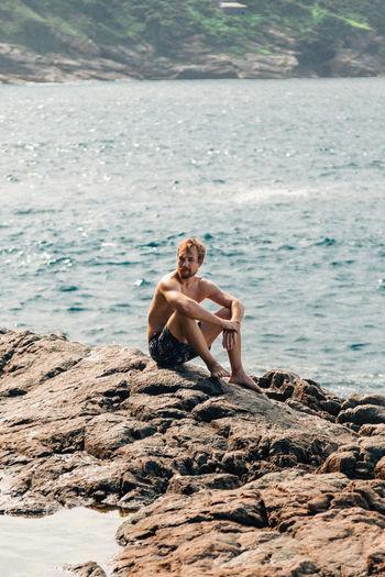 Full length of shirtless man sitting on rock at beach