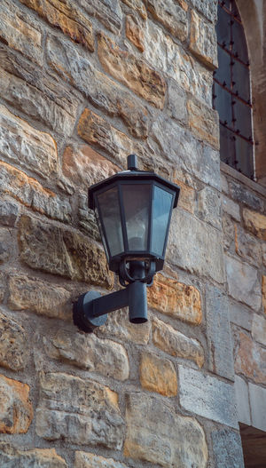 Lighting Equipment Low Angle View Wall Wall - Building Feature Architecture Built Structure Electric Lamp Brick Wall Building Exterior Brick Stone Wall No People Street Light Electric Light Day Mounted Gas Light Building Light Outdoors Light Fixture