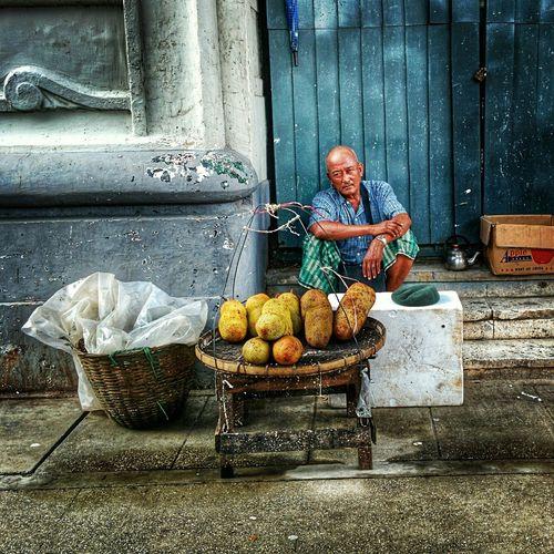 Portrait Of Man Selling Jackfruits Against Building