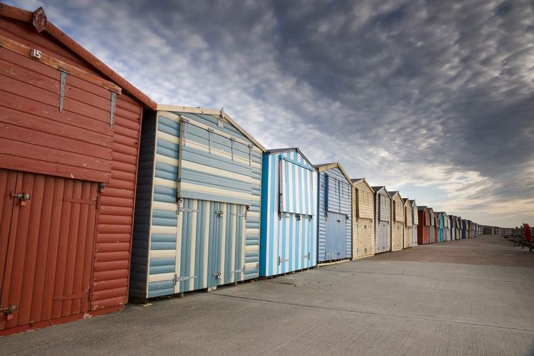 Beach Huts Bright Colors Absence Architecture Beach Hut Beach Huts Building Building Exterior Built Structure Business Closed Cloud - Sky Day Empty Garage Hut In A Row Industry Nature No People Outdoors Seascape Seaside Sky The Way Forward Warehouse