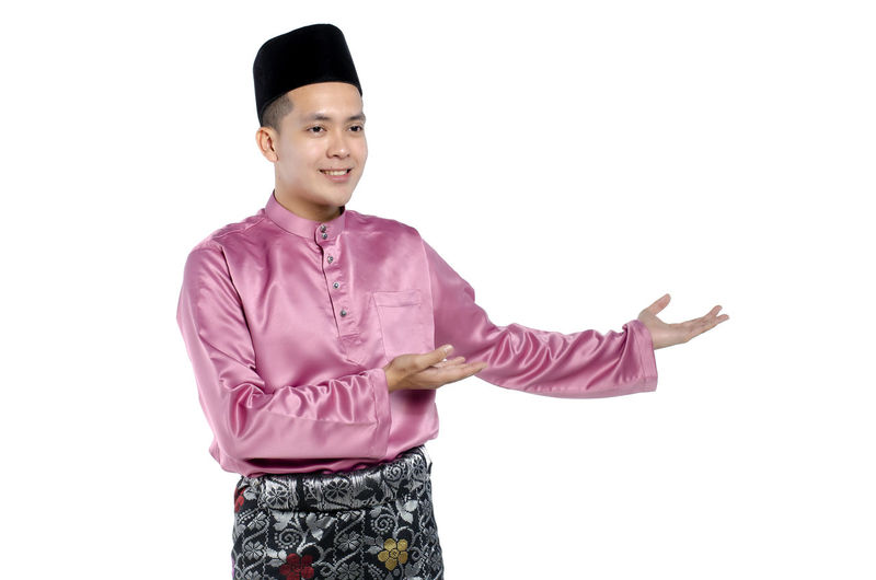 Portrait of young and handsome asian man with traditional clothing during hari raya over white background Studio Shot White Background Standing One Person Front View Indoors  Smiling Looking At Camera Cut Out Waist Up Portrait Gesturing Young Adult Copy Space Young Men Three Quarter Length Casual Clothing Happiness Purple