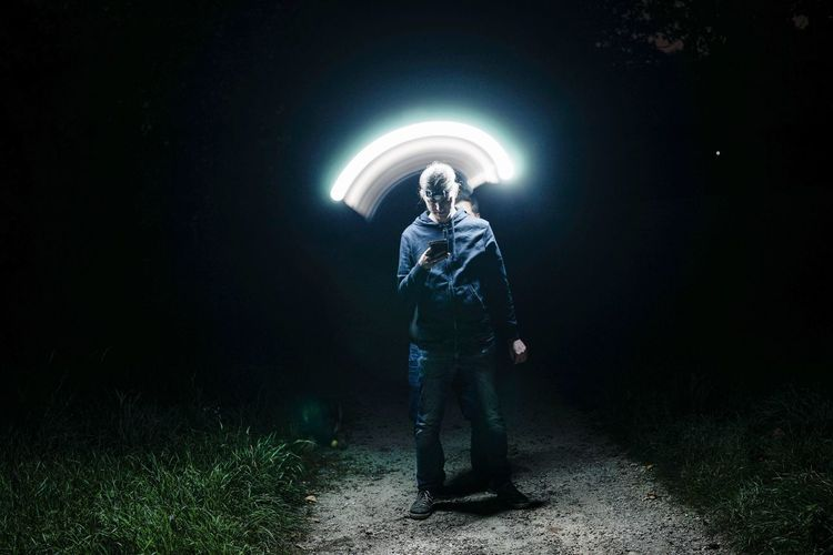 Man looking at illuminated light on field at night