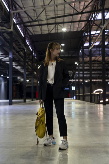 Businesswoman with backpack standing at railroad station