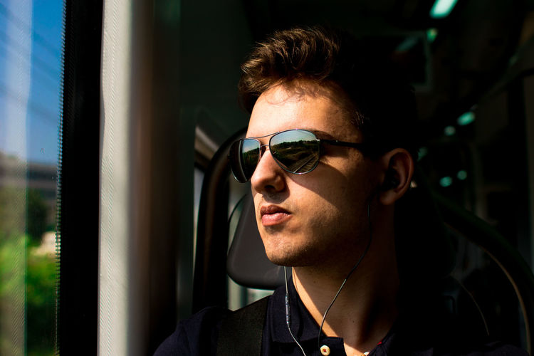 Young man in sunglasses looking away