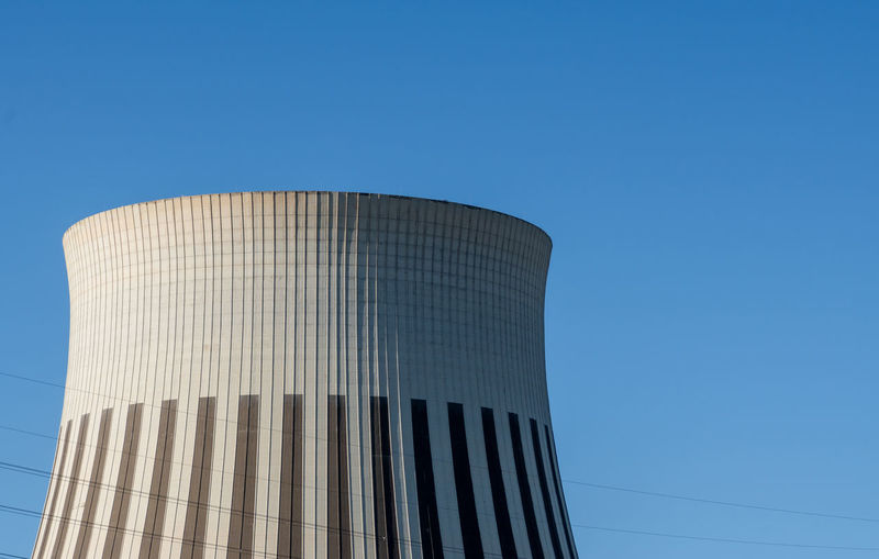 Low angle view of cooling tower against blue sky