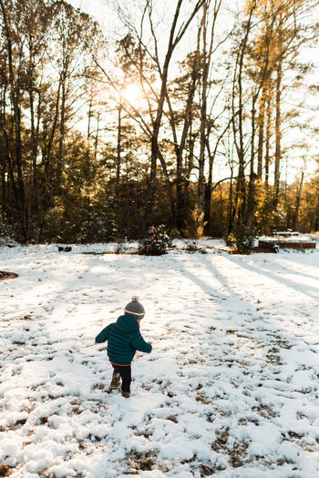 Rear view of child on snow covered landscape