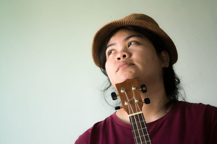 Close-up of woman with ukulele wearing hat against gray background