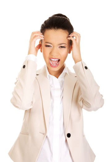 Close-up of businesswoman screaming while standing against white background