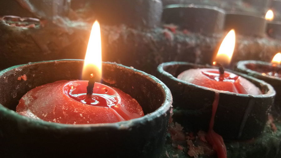 Close-up of burning candles on rock