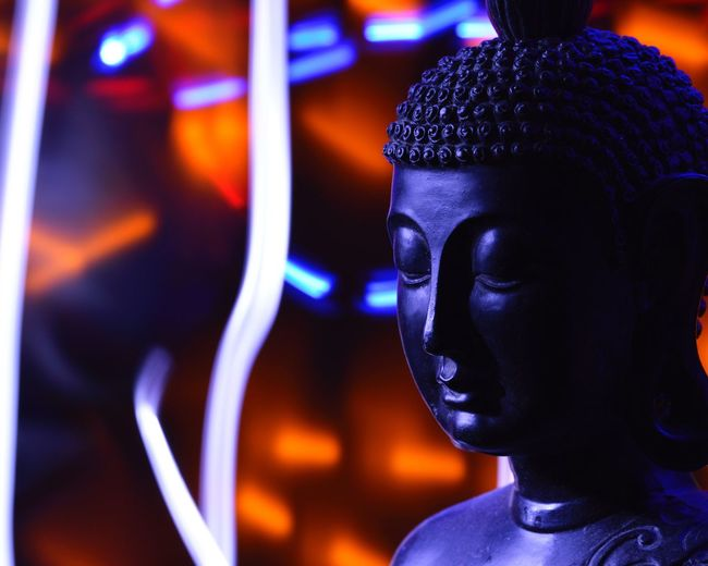 Close-up of buddha statue against illuminated abstract backgrounds