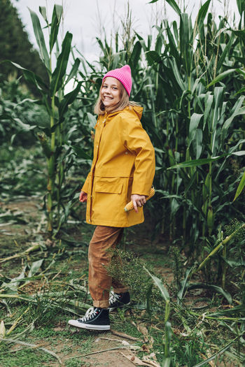 Full length of woman standing against yellow plants