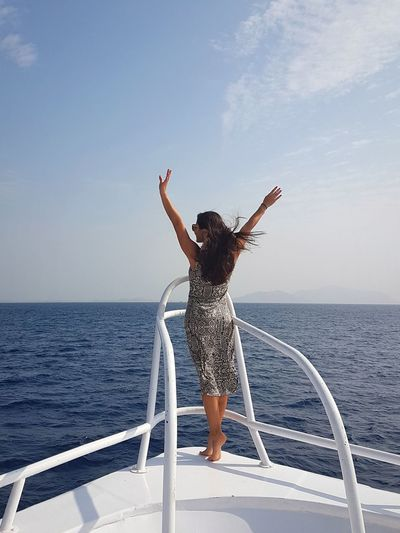 Full length of woman with arms raised against sea against sky