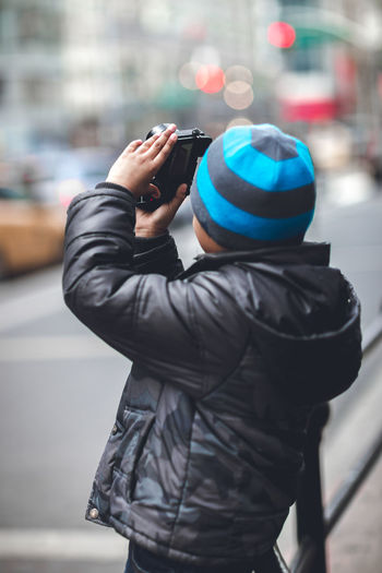 Side View Of Boy Photographing On Street Using Camera