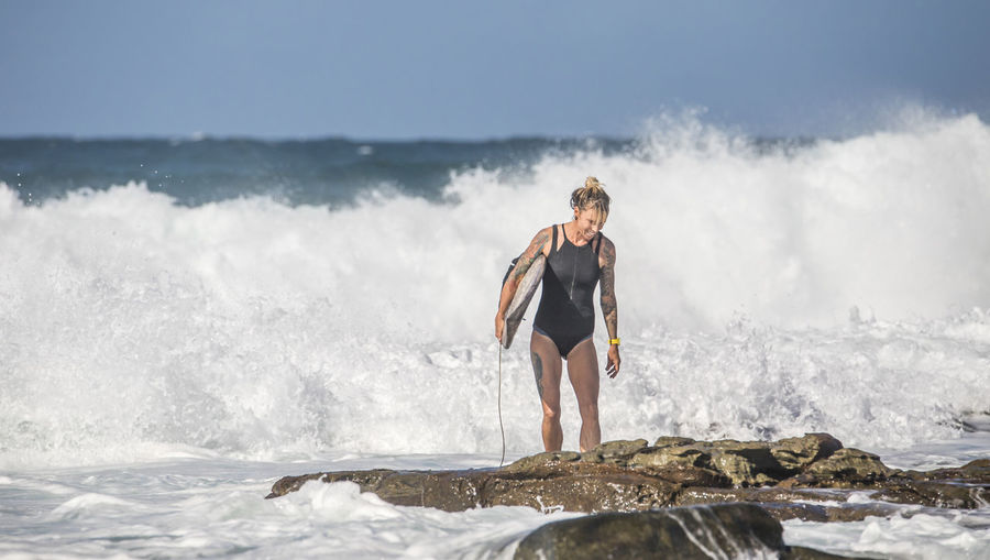 Woman with surfboard standing on rock at sea