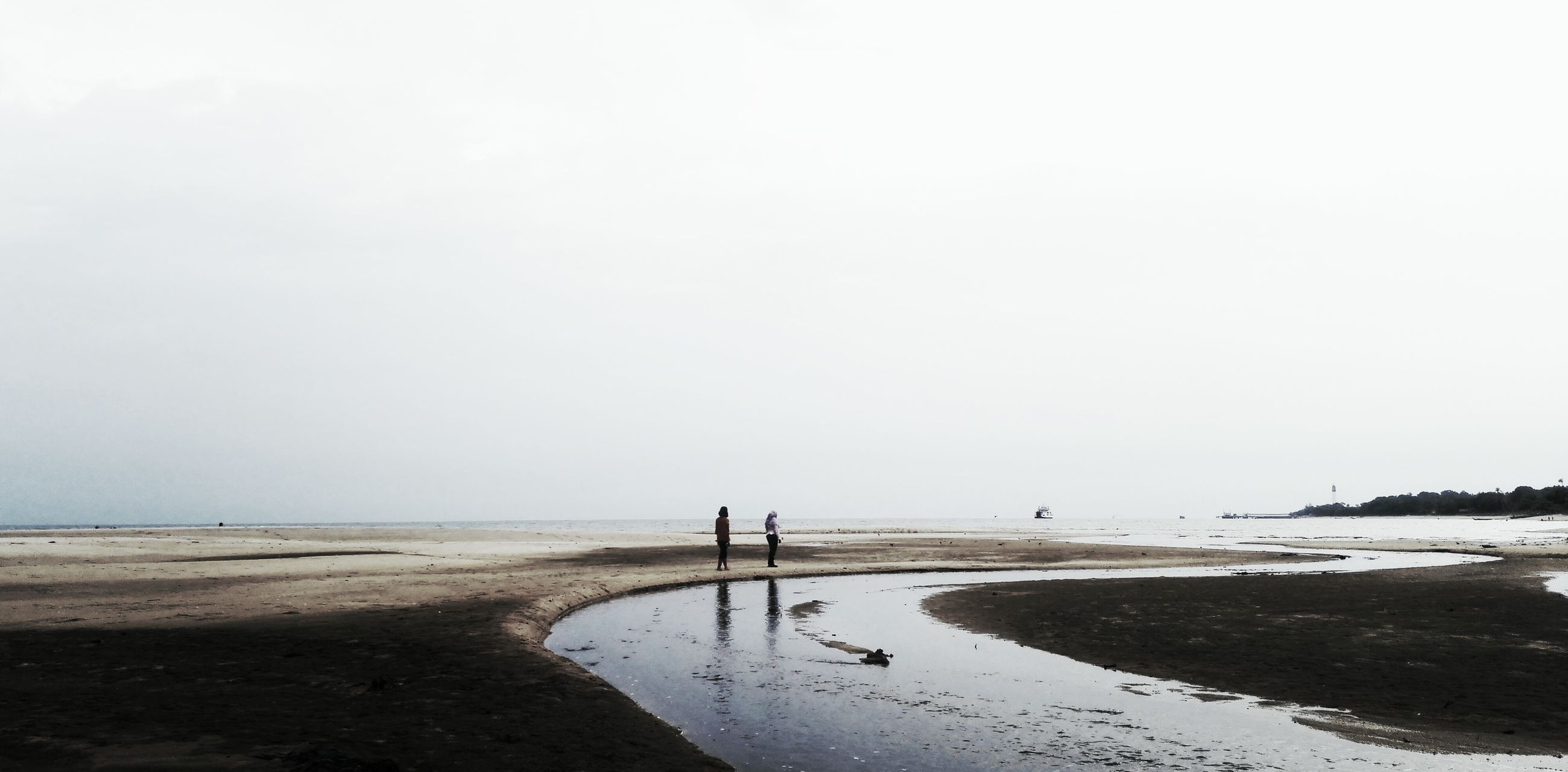 water, beach, clear sky, sea, copy space, tranquil scene, tranquility, sand, shore, scenics, nature, horizon over water, beauty in nature, men, unrecognizable person, silhouette, incidental people, leisure activity
