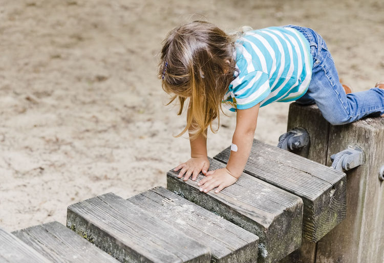 High angle view of child standing on wood