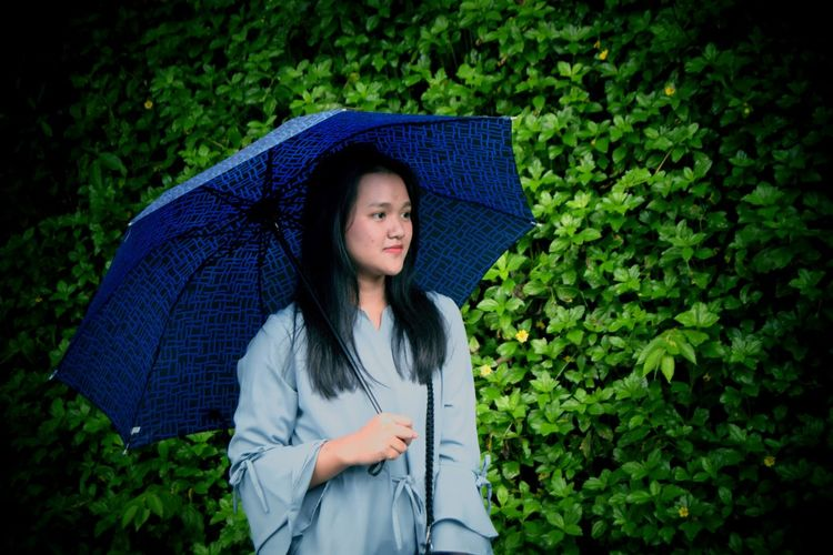 Young woman holding umbrella while looking away against plants in park