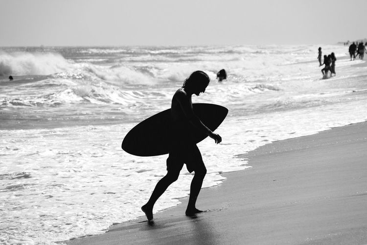 Silhouette Male Surfer Carrying Surfboard At Beach