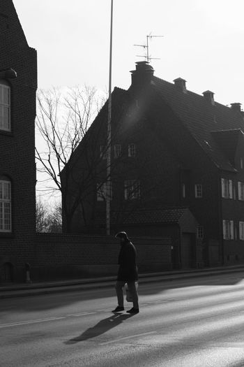 Rear view of man walking on street against buildings in city