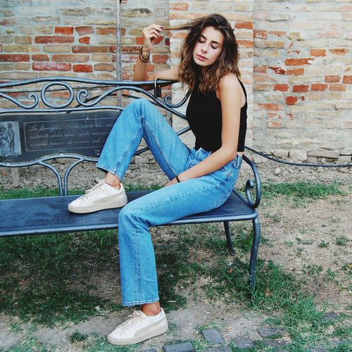 Side view of teenage girl sitting on bench against brick wall