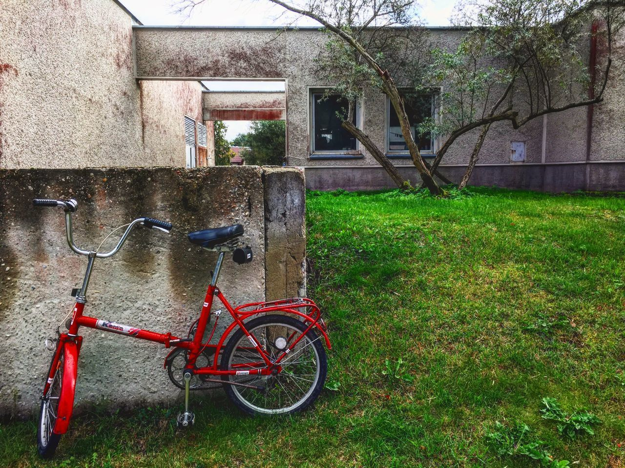 BICYCLE ON FIELD BY HOUSE