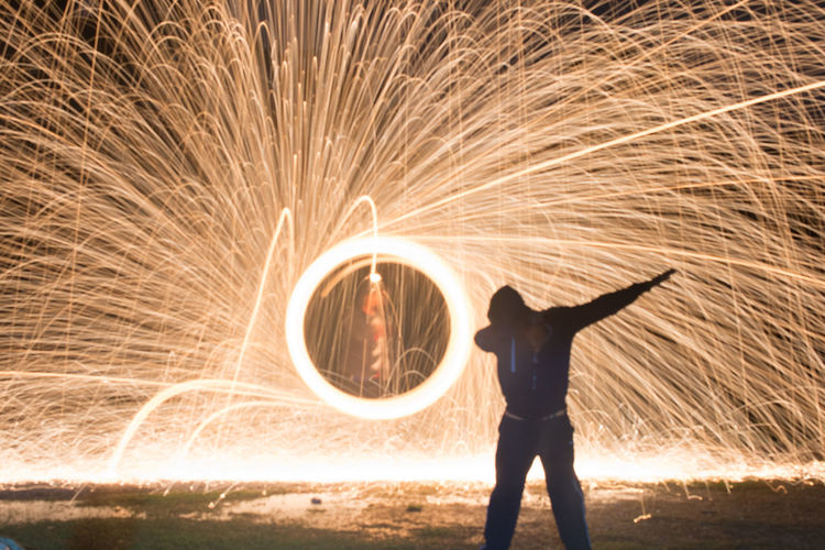 Full Length Of Silhouette Man Standing Against Illuminated Wire Wool At Night