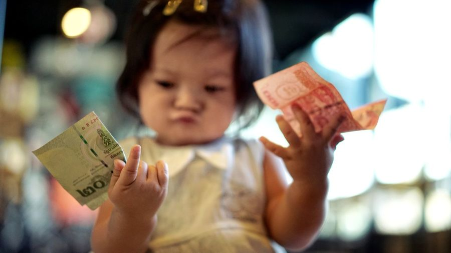 Close-up of girl holding money while sitting indoors