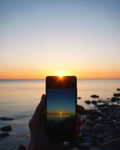 Close-up of hand holding camera on beach against sky during sunset