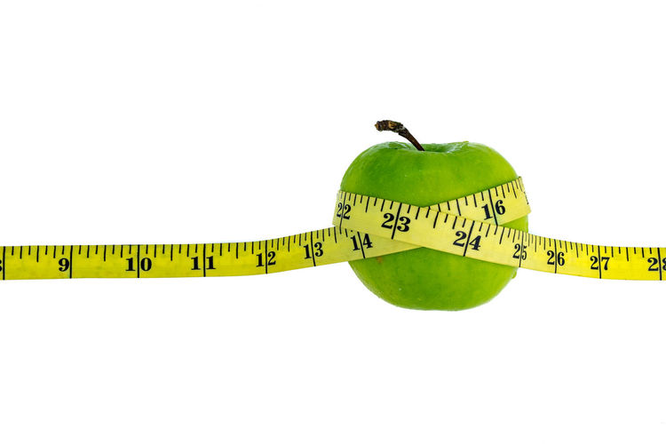 Green apple wrapped with a yellow measuring tape on white background Arrangement Curve Green Green Green Color Healthy Eating Measure Multi Colored Obesity Studio Shot Tape White Background Yellow