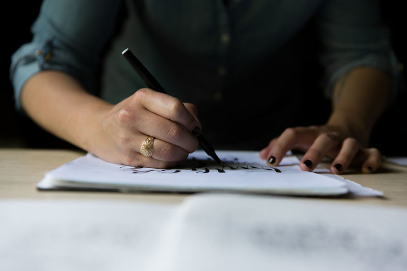 Cropped image of woman drawing on paper at table