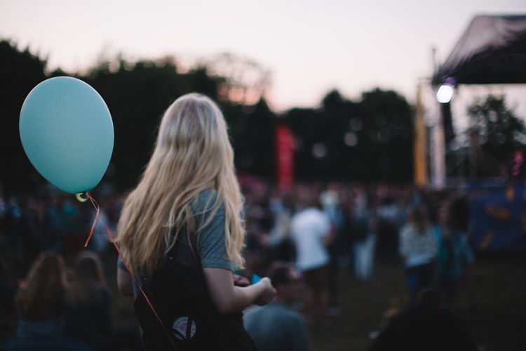 Woman with helium balloon enjoying music concert during sunset