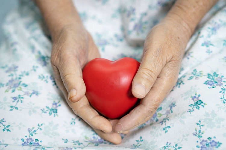 Midsection of woman holding heart shape on table