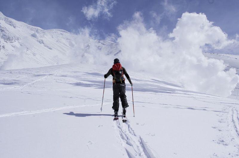Full length of man walking on snowcapped landscape against sky during winter