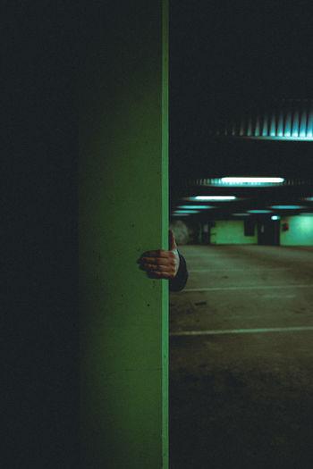 Rear view of man on illuminated wall at night