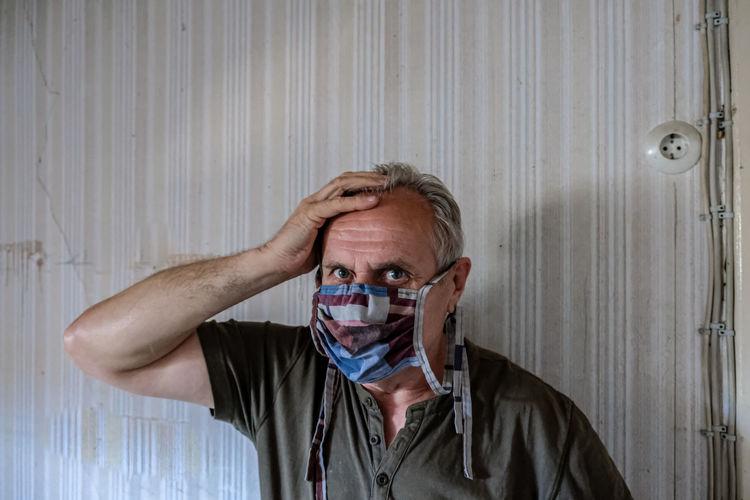 Portrait of senior man wearing flu mask standing against wall