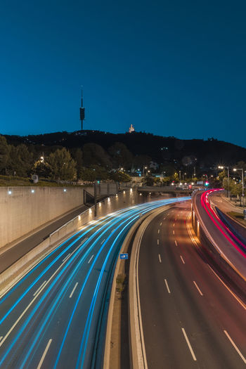 High angle view of light trails on road against blue sky