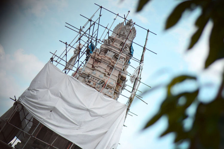 Low angle view of white temple under construction against sky.