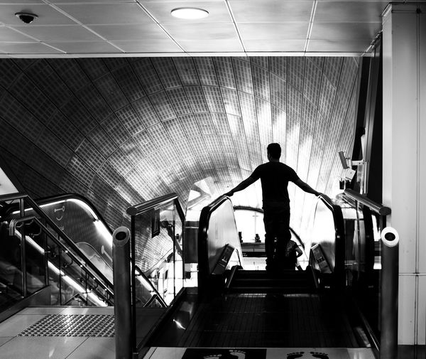 Architecture Blackandwhite Escalator Illuminated Indoors  Lifestyles Modern Monochrome monochrome photography Motion Moving Walkway  One Person Public Transportation Real People Rear View Staircase Steps And Staircases Subway Transportation Walking